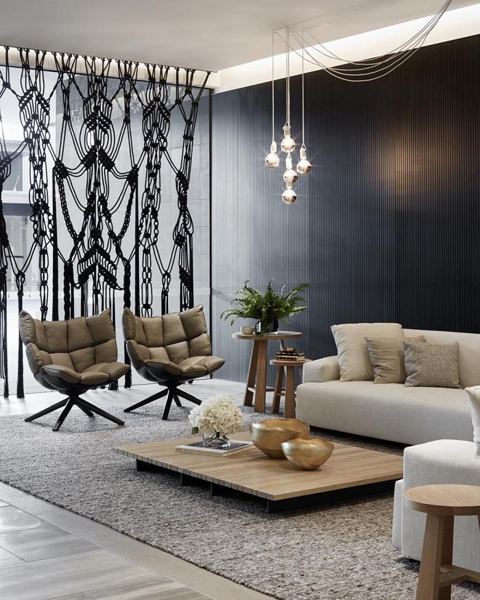 design intérieur moderne aux murs foncés avec suspension luminaire en verre et fauteuil en cuir, idée séparation pièce avec rideaux macramé