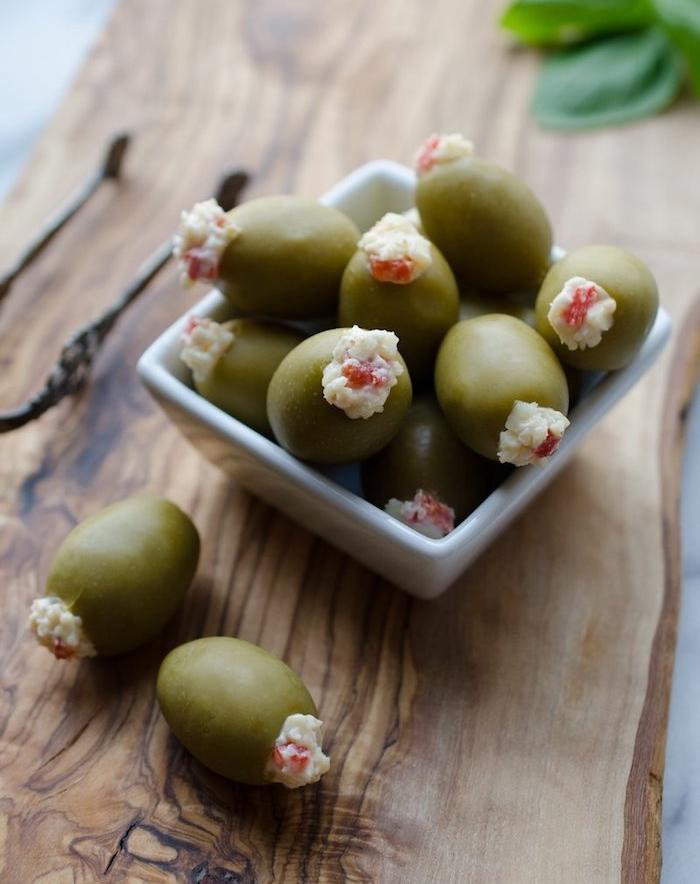 amuse bouche froid, olives vertes farcis de fromage avec des poivrons et lard dans une petite coupelle blanche