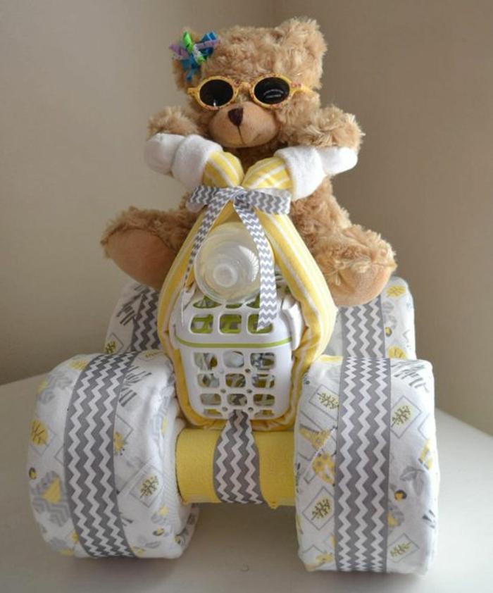un ourson sur une moto composée de linge de lit et des serviettes pliées pour former des roues, animal en peluche marron clair, deco baby shower garcon
