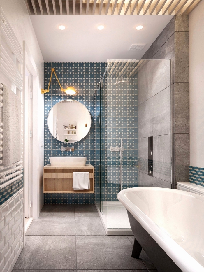 une salle de bains moderne en gris avec faience carreaux de ciment à motifs subtils en bleu canard qui définit l'espace derrière le lavabo