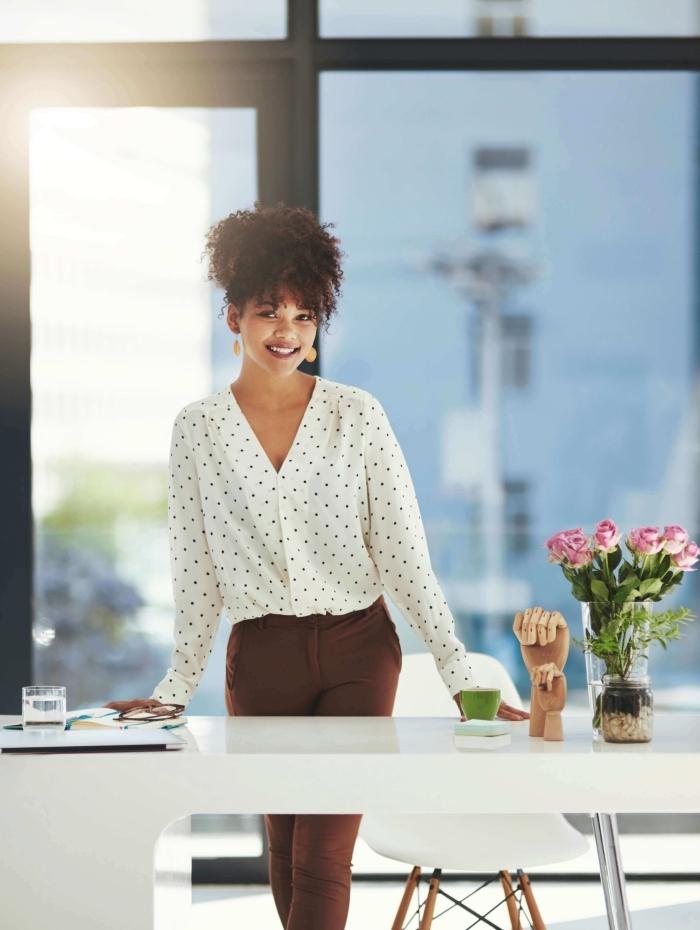 coiffure pour cheveux longs crépus attachés en afro puff avec mèches tombantes devant, tenue vestimentaire au travail avec chemise blanche et pantalon marron