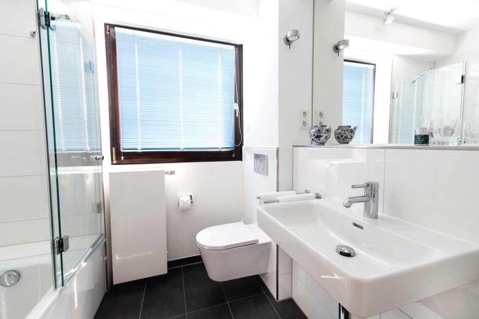 aménagement de petite salle de bain blanche avec large miroir, équipement salle de bain avec baignoire douche et cuvette wc suspendue