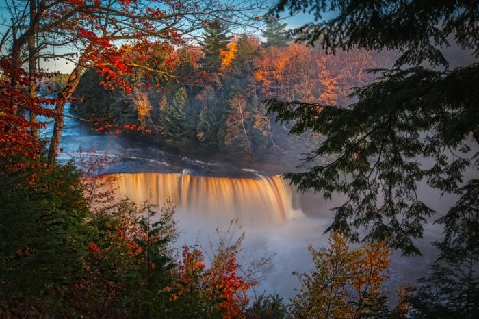 grande chute d'eau au coucher du soleil, arbres au feuillage rouge, ciel bleu