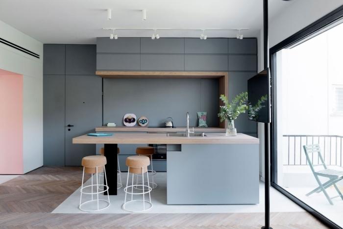 cuisine minimaliste de style scandinave aux lignes épurées équipée d'un ilot central table en bois naturel avec coin repas intégré