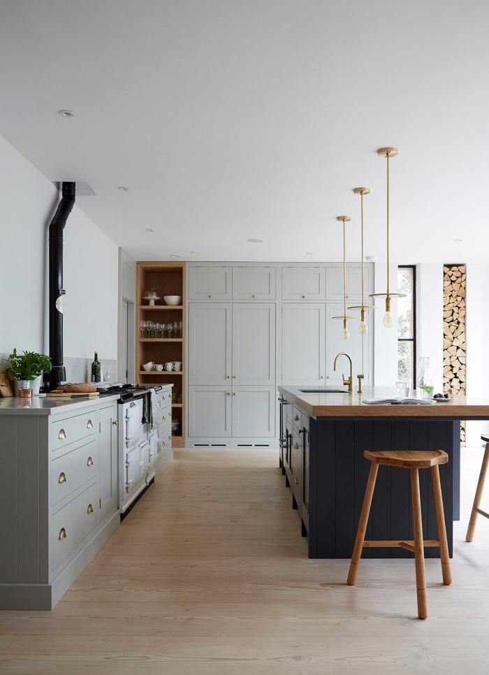 cuisine gris clair d'esprit rustique et vintage avec un ilot centrale de lavage contrastant en gris anthracite et bois, accentué par des luminaires suspendus minimalistes et un robinet doré