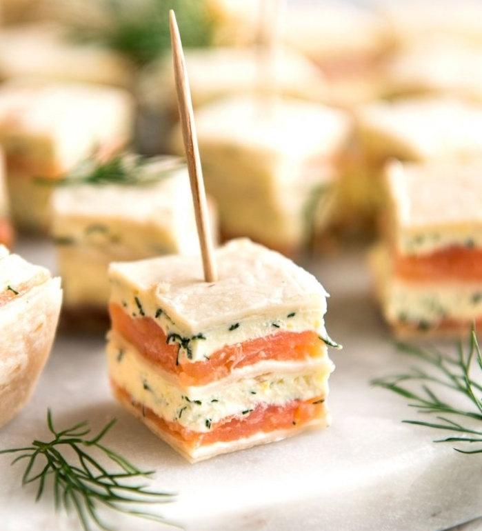 cure dent qui transperce un petit sandwich avec du fromage aux herbes et saumon fumé, apero dinatoire amuse bouche