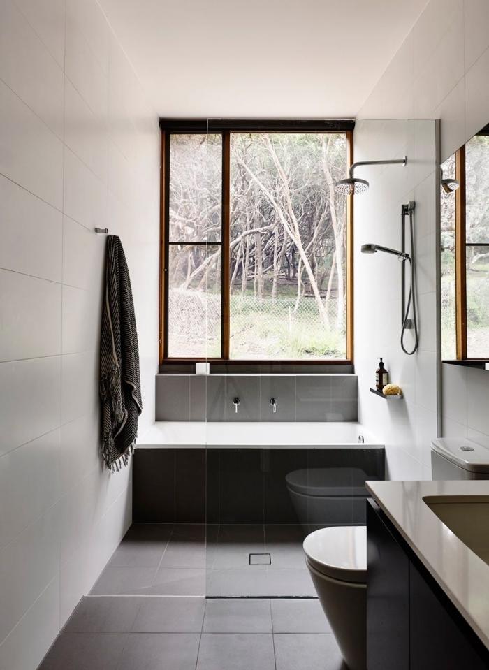 modele de salle de bain espace limité aux murs blancs avec plancher en carrelage gris foncé, modèle petite baignoire