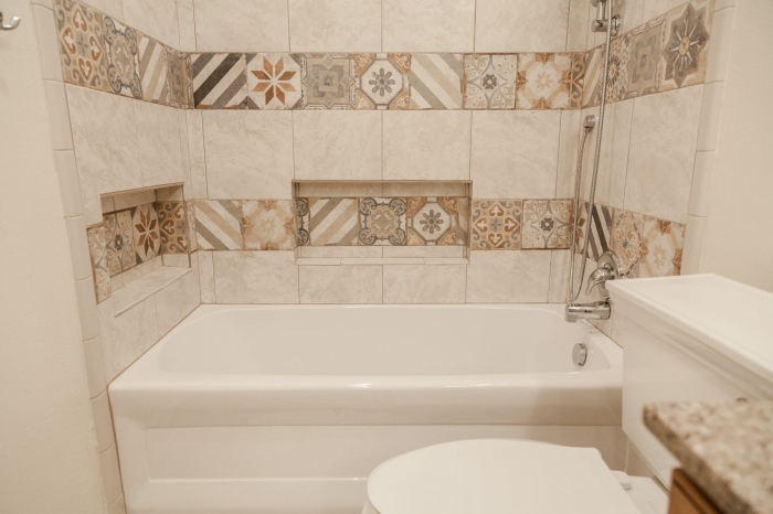 modele de salle de bain aux murs en carrelage imitation carreaux de ciments de couleurs beige avec petite baignoire douche
