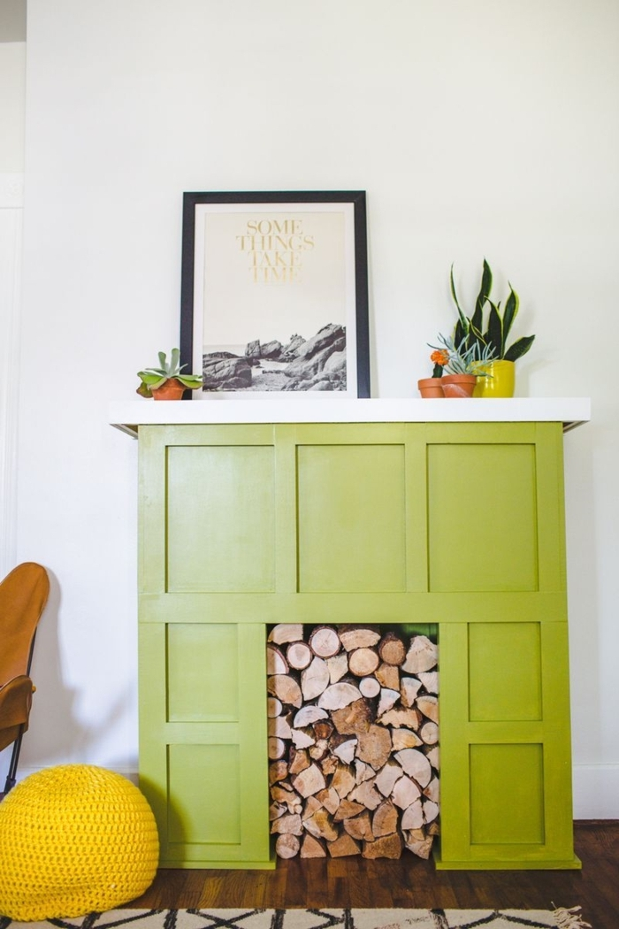 pouf jaune, cheminee deco verte, cadre peinture, pots avec cactus, mur blanc