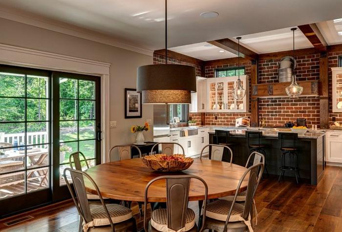 espace design loft industriel, table ronde de bois, chaises métalliques, lampe pendante, mur en briques