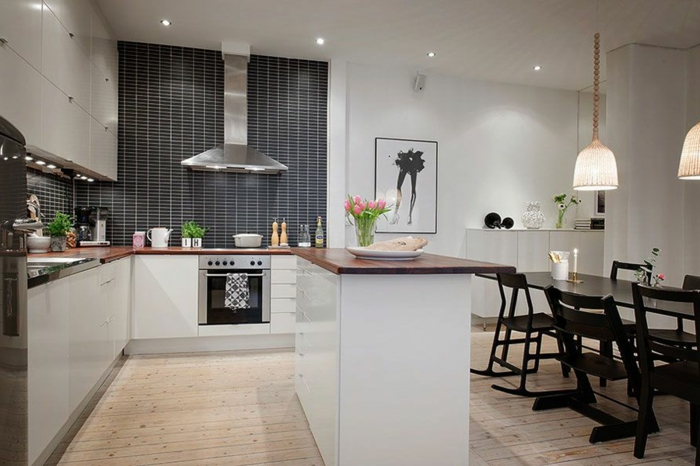 comptoir de cuisine dans une cuisine scandinave et sol en planches, grande table de repas noire, crédence gris anthracite