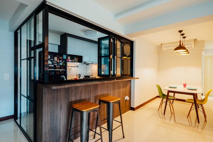 cuisine avec verriere au cadre noir, tabourets en bois et métal, carrelage métro, petite table avec deux chaises scandinaves