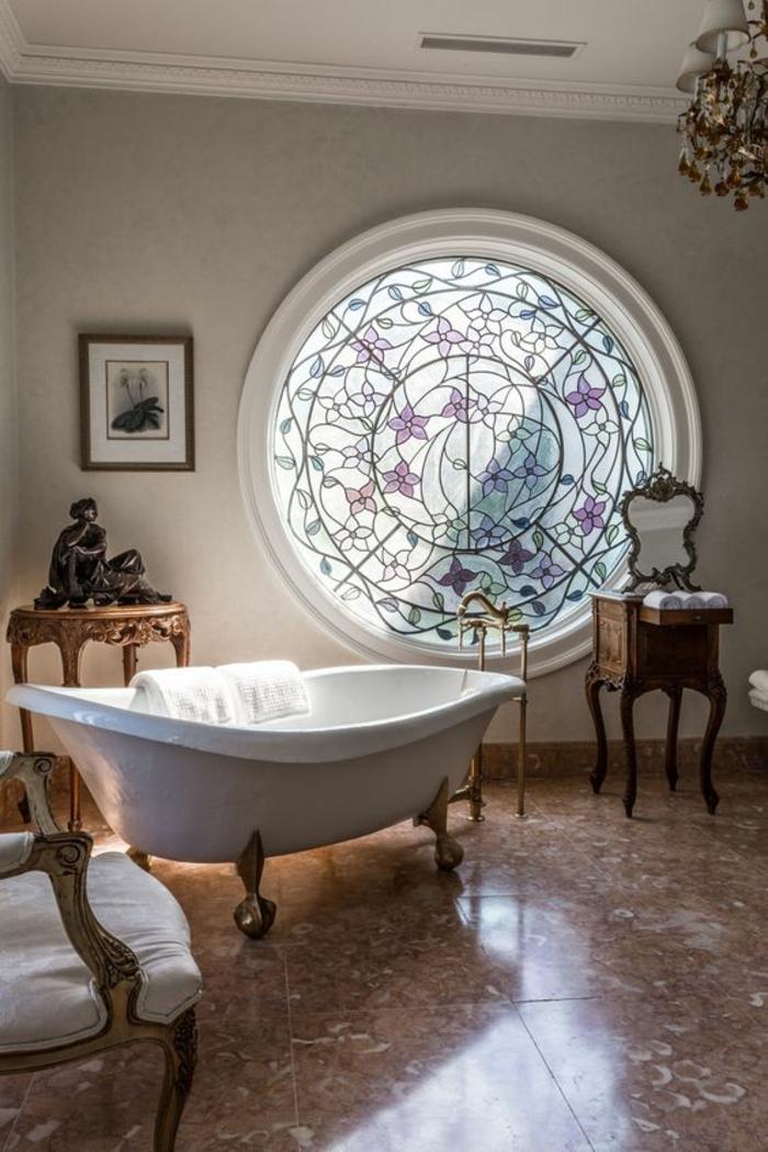 petite salle de bain avec baignoire, grande fenêtre ronde avec des vitraux colorés, modele carrelage salle de bain, salle de bain zen et chaleureuse