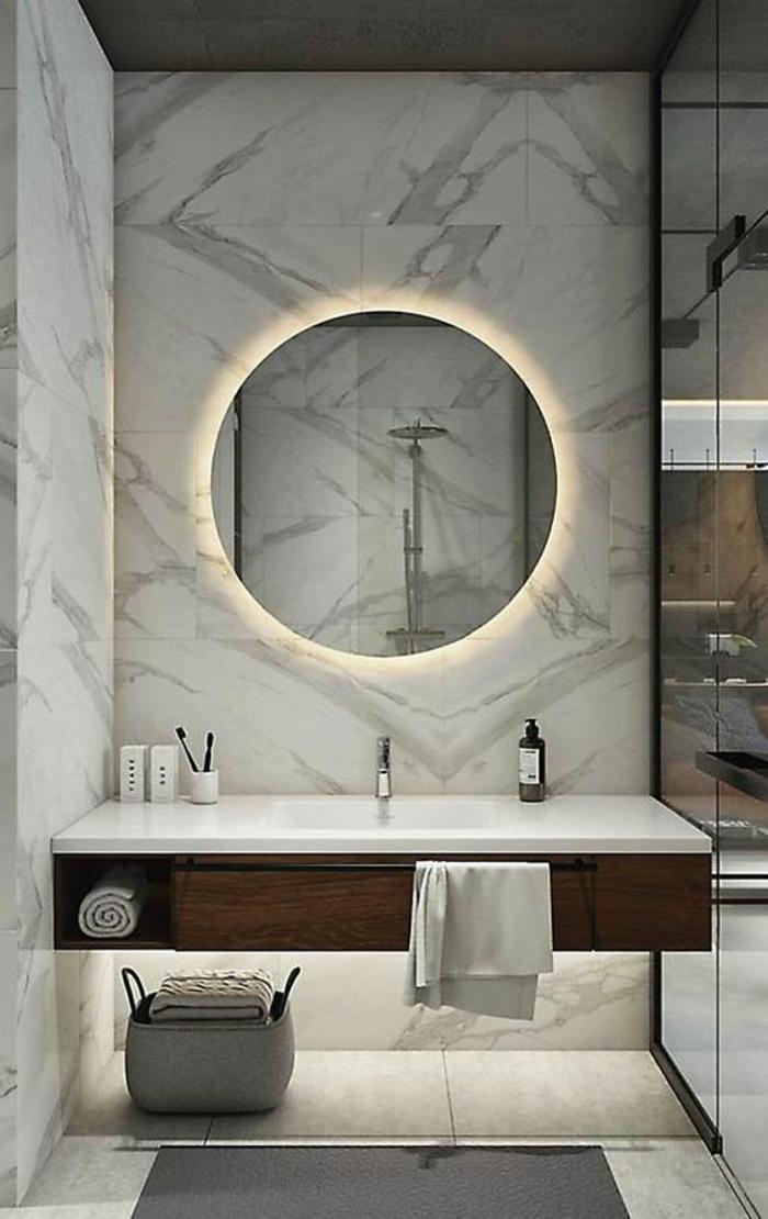 idee salle de bain, murs revêtus de marbre blanc aux nervures noires, pinterest salle de bain, grand miroir rond, discrètement illuminé par derrière