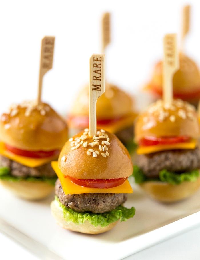 mini hamburger brochette apéritif avec des boulettes, laitue, fromage et tomate dans une assiette blanche