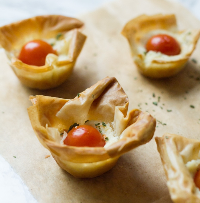 tartalette en pate feuilletée recette avec du fromage aux herbes et tomate cerise en top, idée amuse gueule apero