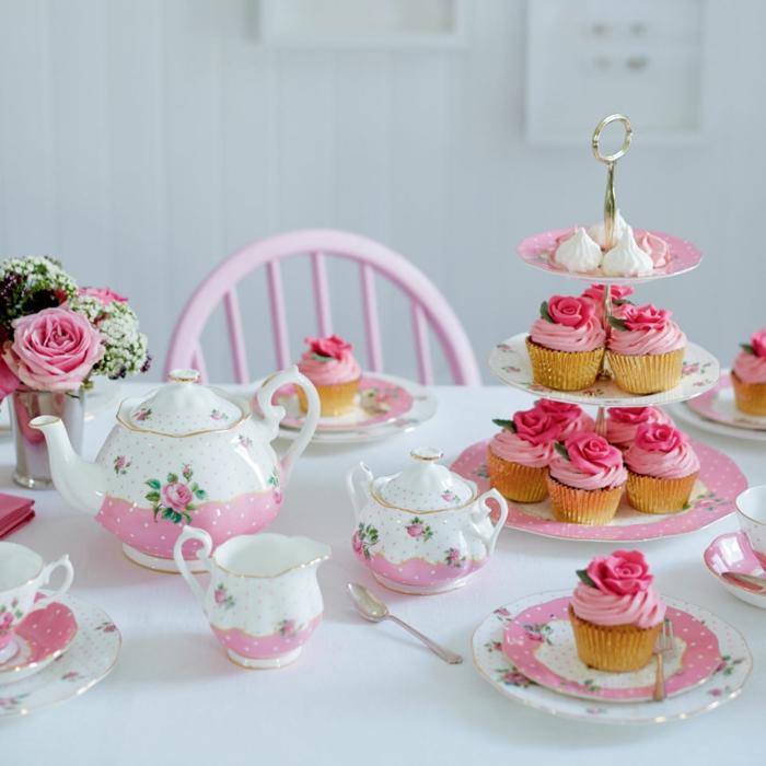 joli gâteau de petits cakes, ustensiles en rose et blanc, petit bouquet de roses, table blanche, chaise rose