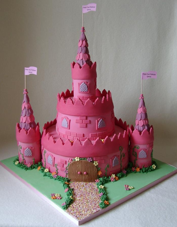 gateau d'enfant artistique, chateau rose avec trois tours, drapeaux, plaine verte