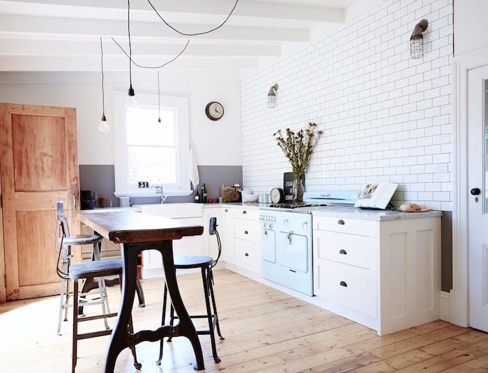 meuble bas cuisine campagne chicavec piani de cuisson bleu pastel, parquet bois clair, carrelage mural metro blanc, armoire bois clair, suspensions ampoule