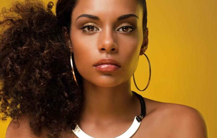 coiffure cheveux crépus, exemple de afro puff inversé avec volume sur les pointes et cheveux lissés sur le haut, coiffure cheveux attachés sur le côté