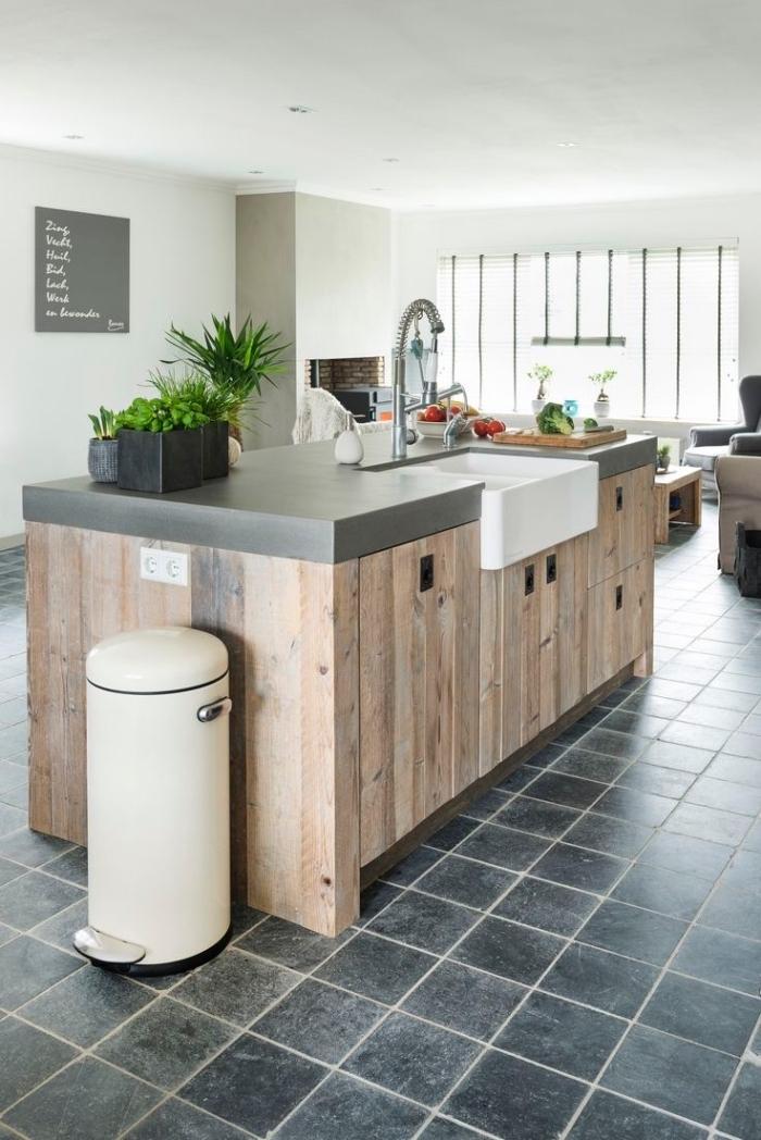 plan de travail ilot central en béton et planches de bois au look rustique avec une zone de lavage dans une cuisine conviviale ouverte sur le salon