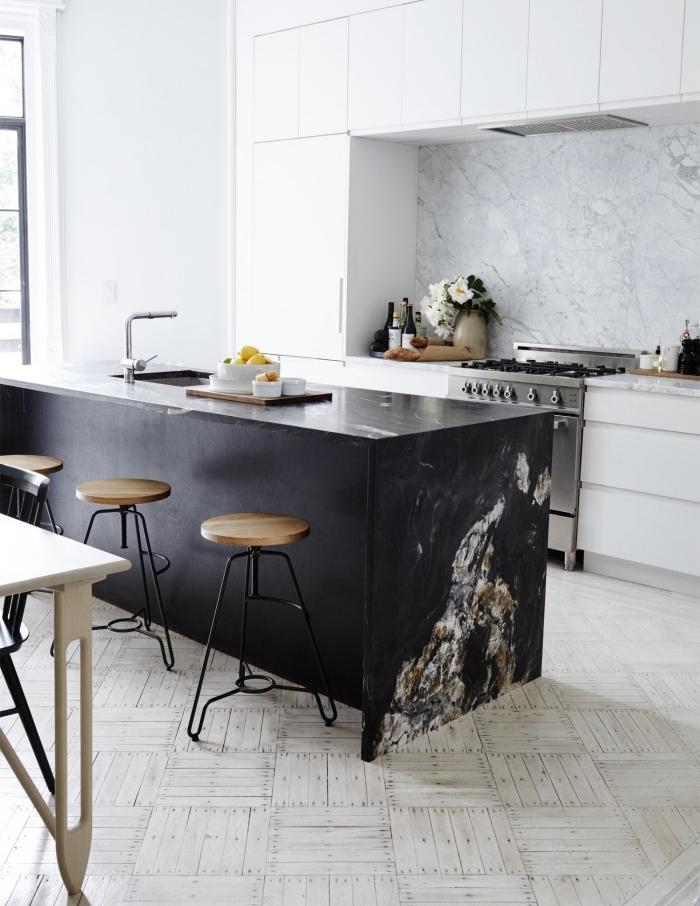 ilot centrale minimaliste en noir mat avec un plan de travail de caractère en marbre noir en contraste avec les armoires blanches