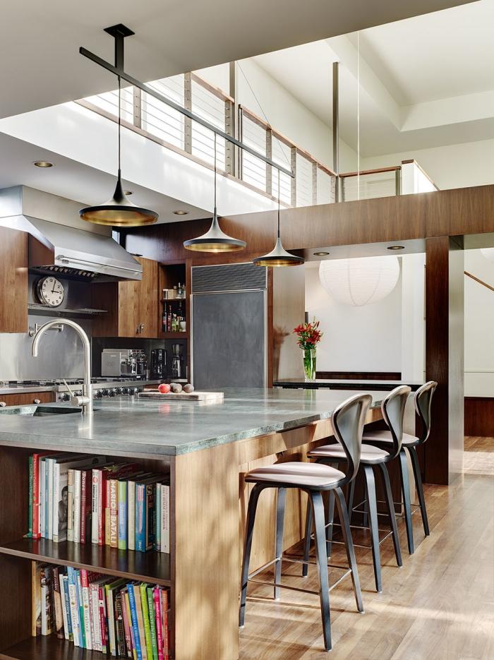 ilot central cuisine ouverte associant un plan de travail en quartz avec espace lavage et une façade en bois, étagères intégrées dans l'îlot de cuisine pour y ranger ses livres de cuisine