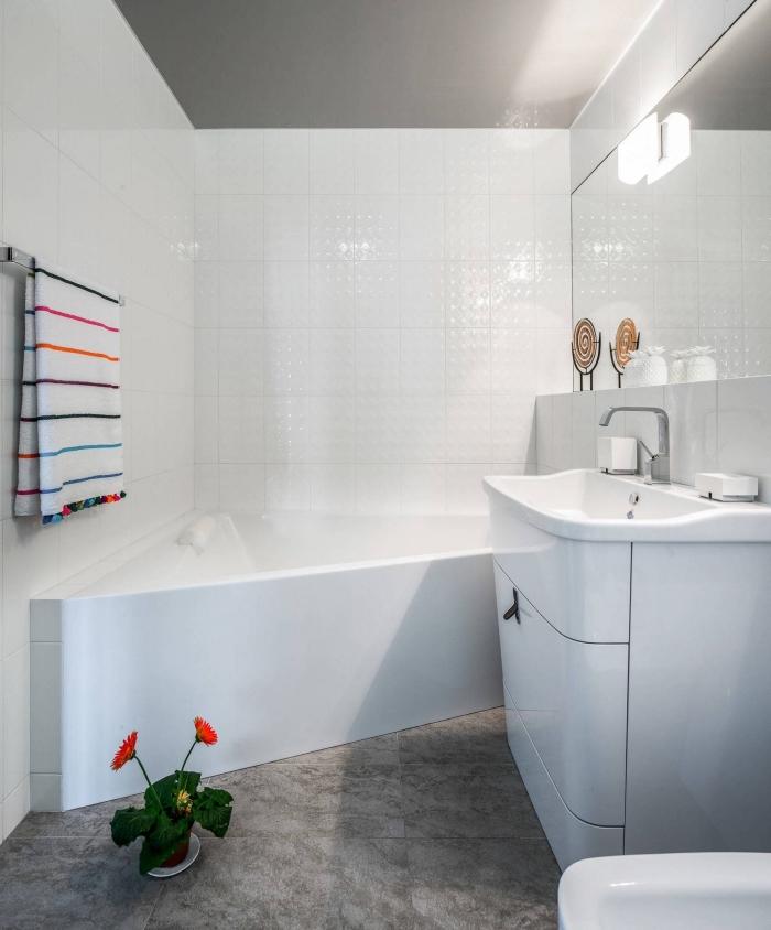 idée décoration de salle de bain blanche au plancher en carrelage imitation béton avec serviette colorée et fleurs