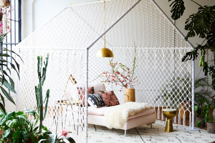 décoration exotique de style jungalow dans un salon blanc aménagé avec meubles de bois et finitions dorées avec plantes vertes, exemple création en macramé