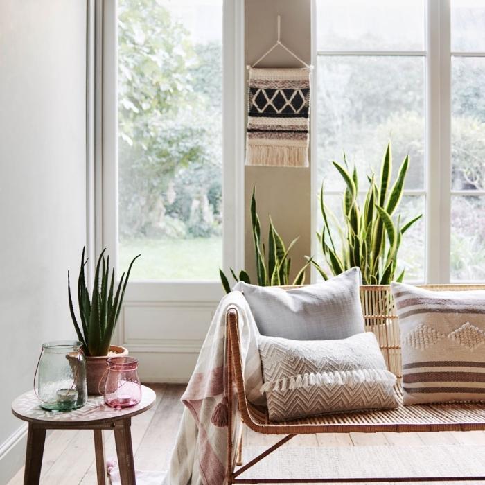 salon ethnique aux murs blancs avec pan de mur taupe et meubles en bois et ratan, objet déco DIY facile en macramé technique