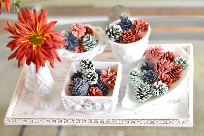 composition deco automne, creation en pommes de pin colorées de peinture couleurs variées et soliflore avec fleur rouge dans un plateau de service vintage