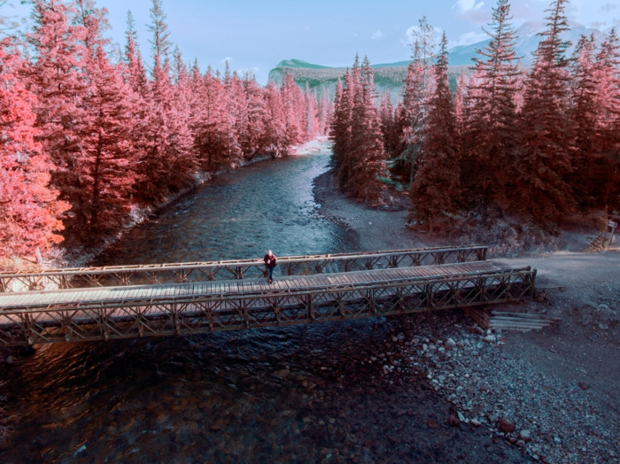 pont traversant une rivière, arbres aux feuilles rougeoyantes, arrière plan montagnes