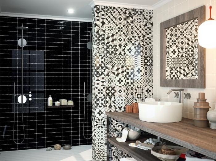 un pan de mur en faience carreaux de ciment à motifs patchwork qui séparent visuellement le lavabo et la douche italienne avec carrelage noir brillant