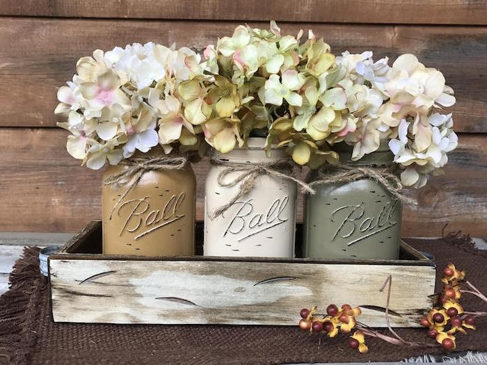 cagette de bois avec des pots en verre repeints et de petits bouquets de fleurs hortensias sur petit tapis tricoté