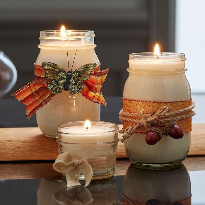 pots en verre bougies DIY décorées de ruban, ficelle, papillon artificielle et des glands artificiels, deco romantique automne