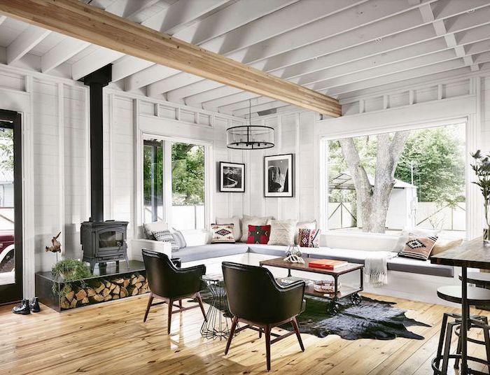 modele de salon chaleureux avec canapé d angle blanc, chaises cuir noires, cheminée noire moderne, table basse bois et métal à rouelttes, suspension originale metallique, tapis peau animal