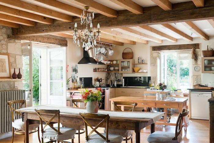 decoration campagne exemple de table et chaises bois brut, parquet clair, poutres apparentes, lustre élégante, meuble cuisine bois