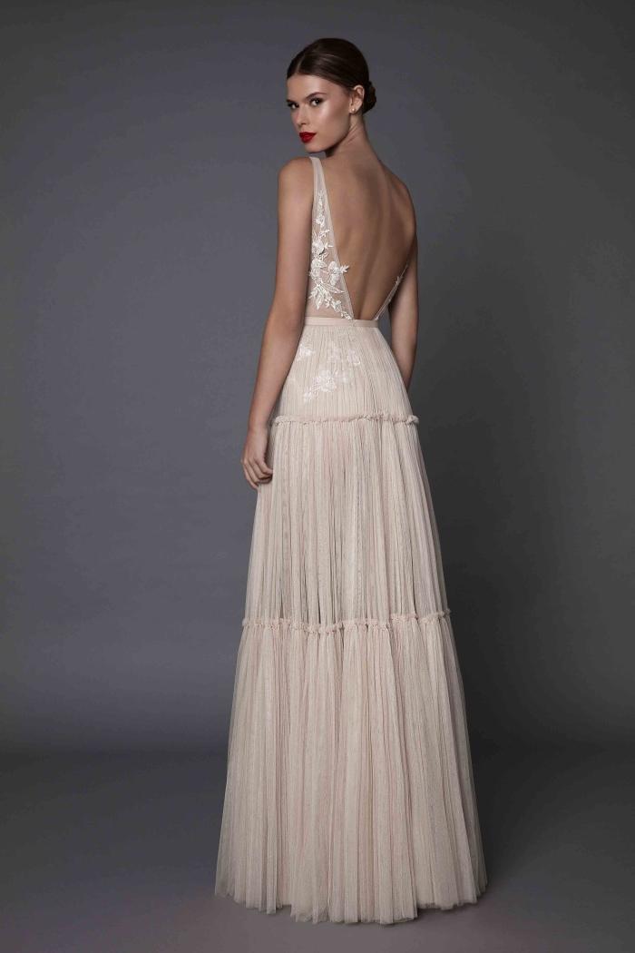 robe mariée dos nu couleur rose beige à bas fluide en contraste avec le design sensuel du bustier avec sa découpe en arrière et
