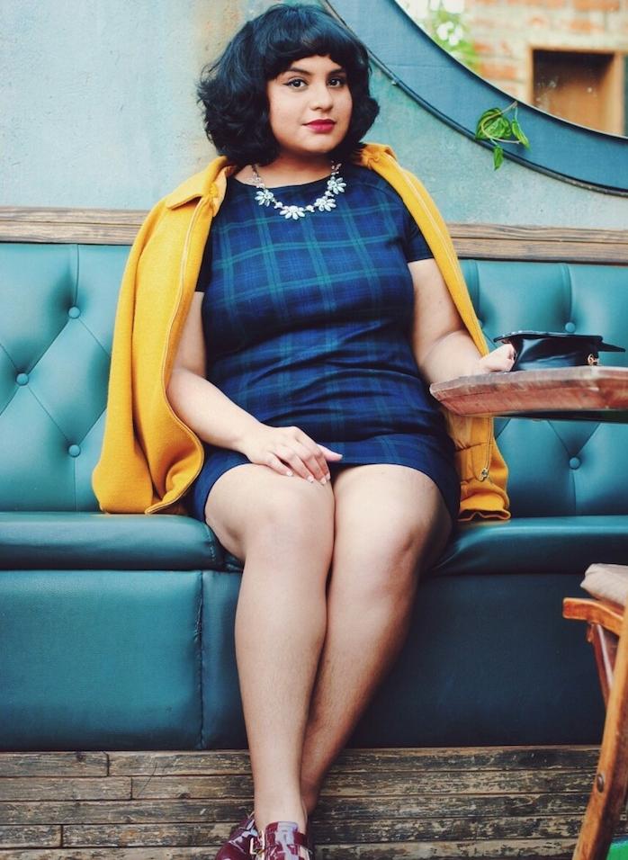 collier à motif fleurs pour accessoiriser une robe droite bleue, veste jaune, femme aux cheveux coupés e carré avec frange