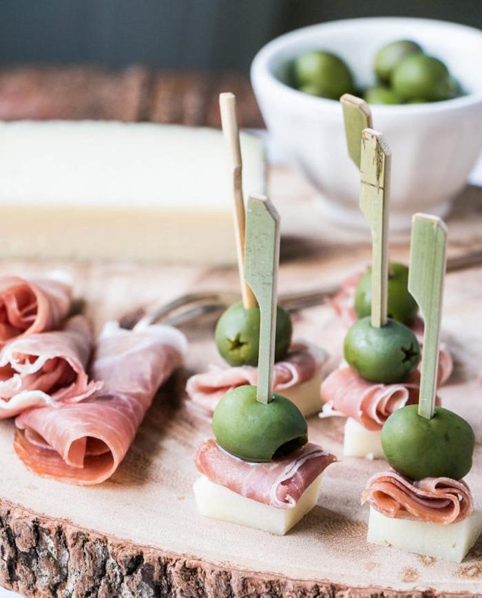 idée de brochette apero simple en fromage manchego, olive et prosciutto servi sur un rondin en bois, repas entre amis