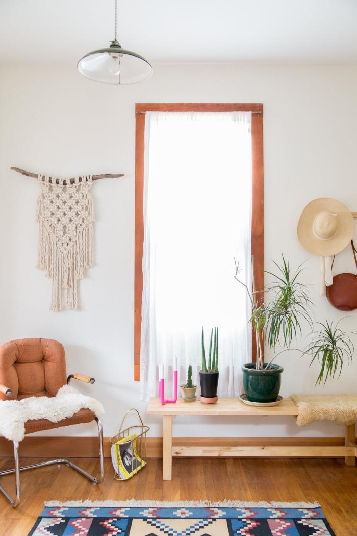 salon à design bohème chic avec meubles de bois et plantes vertes, modèle de macramé mural en bâton bois et corde