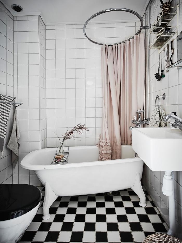 déco cozy dans une petite salle de bain en blanc et noir, modèle petite baignoire sur pieds, rangement gain place en métal