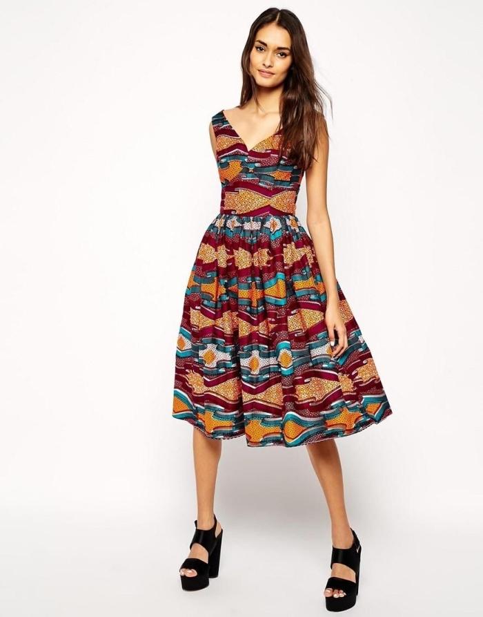 comment porter l'imprimé wax de façon moderne et stylé, une robe midi évasée à col en v, à motifs ethniques en bleu, orange et rouge
