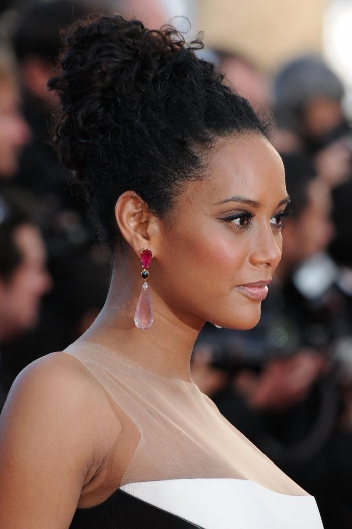 exemple d'un chignon haut sur cheveux longs crépus, maquillage pour peau bronzé avec illuminateur visage et eye liner noir