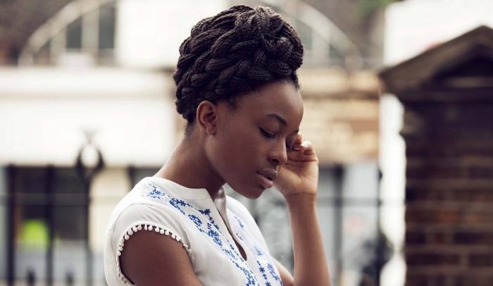 exemple de chignon haut travaillé en petites tresses, idée coiffure de mariée pour cheveux longs et crépus, modèle de robe blanche avec broderie et petits pompons sur les manches