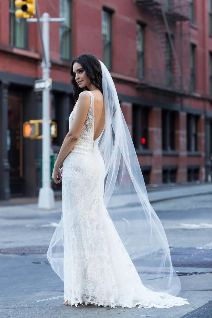 robe de mariée à dos nus d'une coupe élégante ajustée à la taille, recouverte de dentelle et accessoirisé avec un voile léger