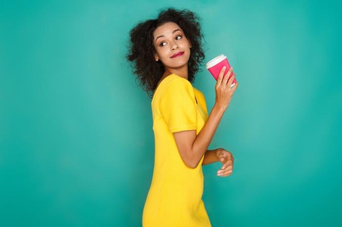 exemple de coiffure de style africain pour cheveux crépus mi longs, coiffure blow out avec une raie et volumes sur les côtés, modèle de robe jaune aux manches courtes