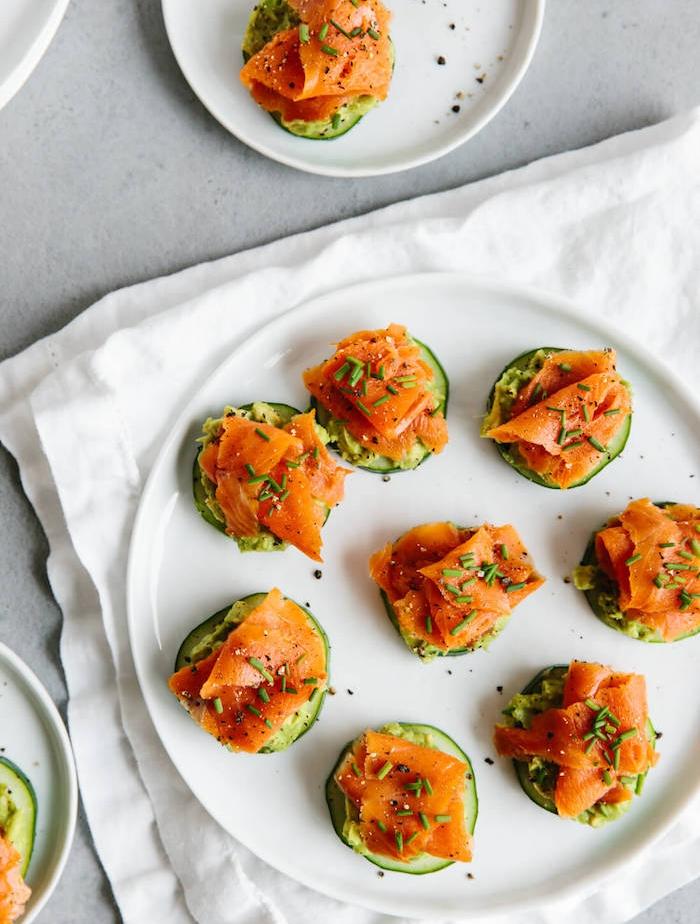 rondelle de concombre avec du pesto et saumon servi avec des herbes fraiches dans une assiette ronde blanche
