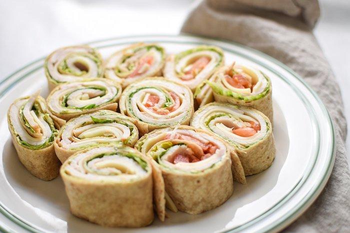 petits rouleaux à la tortilla avec de la laitue et saumon dans une assiette blanche ronde, apéritif dinatoire simple