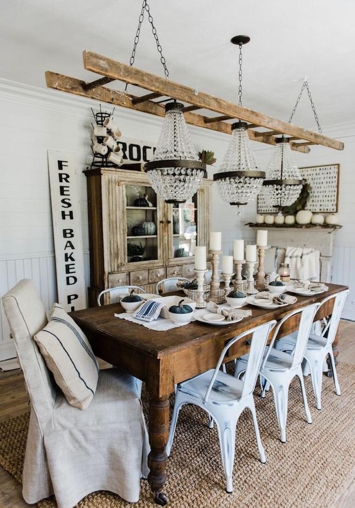 salle à manger style campagne ferme avec table en bois brut, chaises blanches patinées en métal, suspension original echelle et lustres, vaisselier bois brut